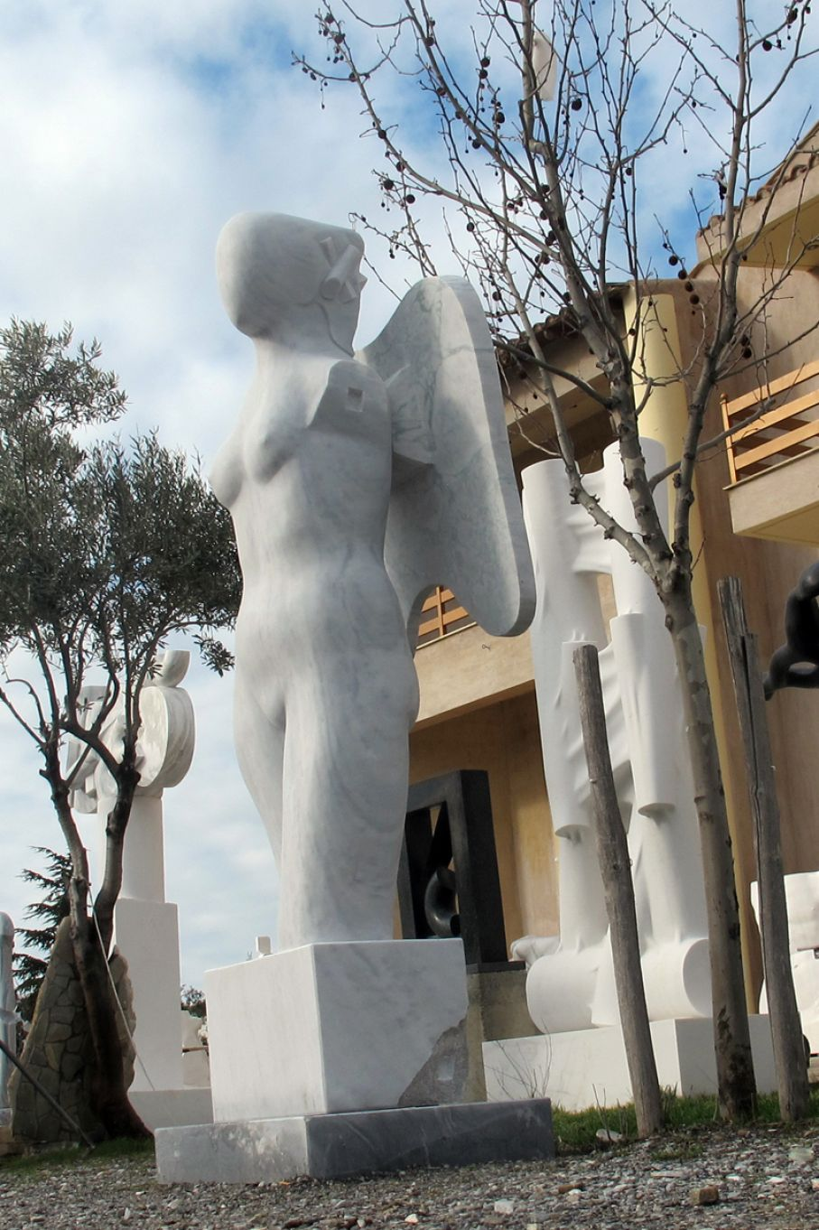 BRIEF DESCRIPTION. Original marble sculpture of  Giorgie Cpajak, completed within Myrό Antiques House premises, in Souroti, Thessaloniki, GREECE, as part of the Greek Marble Initiative. Dimensions: 270 X 92 X 80 cm (with a base and a pedestral as depicted).